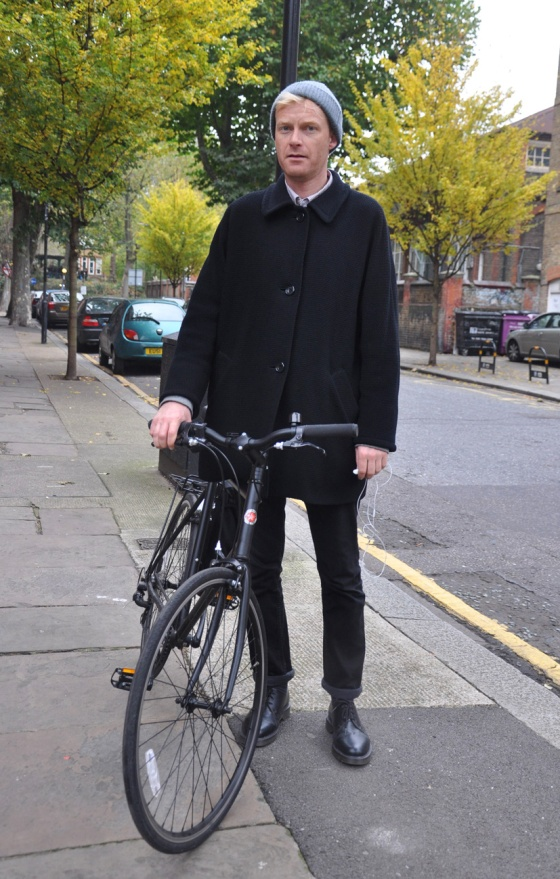 Made in London, Street Style, UK, Gentleman on wheels, Bike, Brick lane, Black coat, boots, wool cap, blonde, british, trees, green, man, trends, fashion blogger, PimPamMate