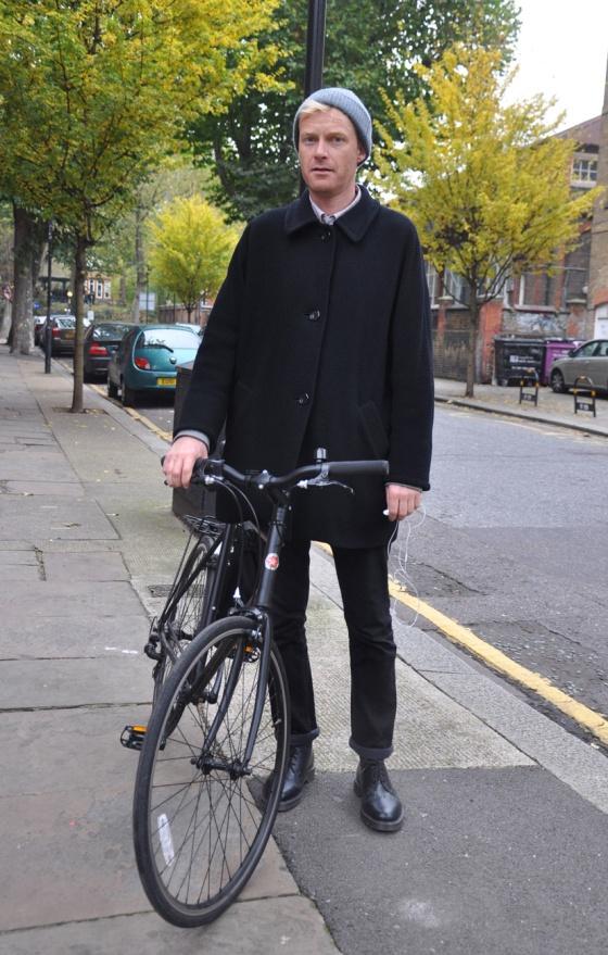 Made in London, Street Style, UK, Gentleman on wheels, Bike, Brick lane, Black coat, boots, wool cap, blonde, british, trees, green, man, trends, fashion blogger, PimPamMate